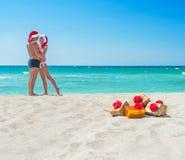 Besando pares de los amantes en los sombreros de santa en el mar vare Imagen de archivo libre de regalías