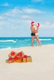 Besando pares en los sombreros de santa en el mar vare con la Navidad de oro Foto de archivo libre de regalías