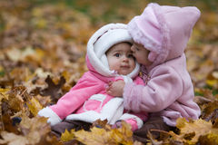 Besar a hermanas en parque del otoño Imagen de archivo