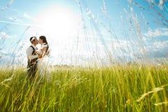 Besar la novia y al novio en hierba asoleada Imagen de archivo libre de regalías