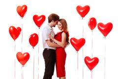 Besar los pares que presentan en el fondo blanco con el corazón de los globos imagen de archivo