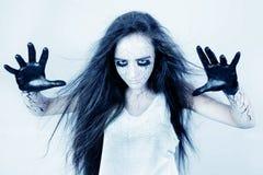 Besatt vid andar, en flicka med blåmärken under hennes ögon och svartåder trollar henne händer begrepp av halloween och dagen av  royaltyfri bild
