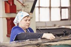 Beschäftigte ältere Arbeitskraft an der Maschine Stockfoto