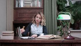 Beschäftigte arbeitende junge Frau, die Anmerkungen macht und auf Kaffee erdrosselt, nachdem er getrunken worden ist stock footage