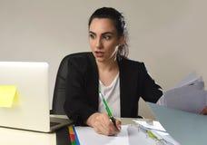 Beschäftigte attraktive Frau im Anzug, der im Druck hoffnungsloses schreibend überwältigt arbeitet Stockfotografie