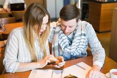 Beschäftigte Bloggers, die im Café mehrere Dinge gleichzeitig tun Stockfoto