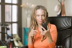 Beschäftigte Frau mit Drealocks zeigend auf ihr Telefon Stockfotografie