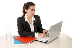 Beschäftigte Geschäftsfrau, die einen Anzug arbeitet an Laptop trägt Stockfoto