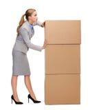 Beschäftigte Geschäftsfrau, die Turm von Pappen drückt Lizenzfreies Stockbild