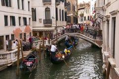 Beschäftigte Kanal-Brücke mit Gondolieren in Venedig Italien Lizenzfreie Stockfotos