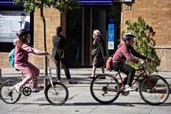 Beschäftigte Leute, die in die Straßen von Sevilla 40 radfahren Stockfotos