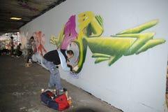 Beschäftigte Malereigraffiti des Straßenkünstlers auf einer bloßen Wand Lizenzfreies Stockfoto