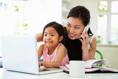 Beschäftigte Mutter, die vom Haus mit Tochter arbeitet lizenzfreie stockbilder
