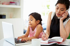 Beschäftigte Mutter, die vom Haus mit Tochter arbeitet Stockfotos