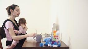 Beschäftigte Mutter mit Baby im Büro der Riemen-Fördermaschine zu Hause, das an Unterhaltungsfütterungsmultitasking des telefons  stock video
