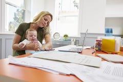 Beschäftigte Mutter mit Baby-laufendem Geschäft vom Haus lizenzfreie stockbilder