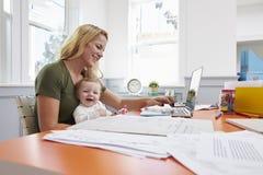 Beschäftigte Mutter mit Baby-laufendem Geschäft vom Haus stockfotografie