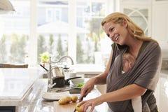 Beschäftigte Mutter mit dem Baby im Riemen zu Hause mehrere Dinge gleichzeitig tuend stockbild