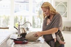 Beschäftigte Mutter mit dem Baby im Riemen zu Hause mehrere Dinge gleichzeitig tuend stockbilder