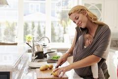 Beschäftigte Mutter mit dem Baby im Riemen zu Hause mehrere Dinge gleichzeitig tuend stockfotografie