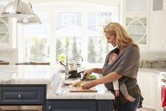 Beschäftigte Mutter mit dem Baby im Riemen zu Hause mehrere Dinge gleichzeitig tuend stockfotos