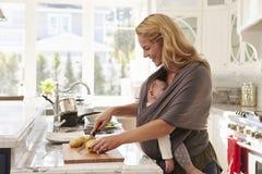 Beschäftigte Mutter mit dem Baby im Riemen zu Hause mehrere Dinge gleichzeitig tuend lizenzfreie stockfotos