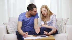 Beschäftigte Paare mit Papieren und Taschenrechner zu Hause stock footage