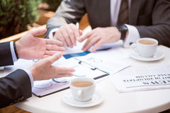 Beschäftigte starke Kollegen, die am Tisch sitzen Stockfotografie
