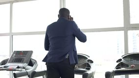 Beschäftigter afro-amerikanischer Mann in der Klage, die auf Tretmühle läuft und am Telefon spricht stock video footage
