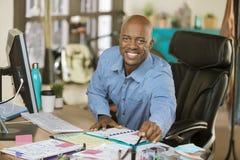 Beschäftigter Afroamerikaner-Geschäftsmann im Büro Stockbilder