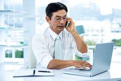 Beschäftigter asiatischer Geschäftsmann, der an Laptop und dem Nennen arbeitet Stockfoto