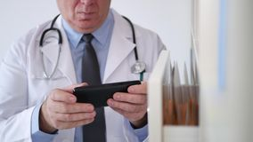 Beschäftigter Doktor im Krankenhauskabinetttext unter Verwendung der drahtlosen Verbindung des Mobiltelefons stock video footage