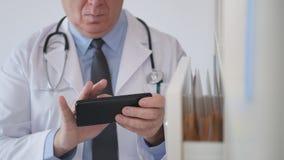 Beschäftigter Doktor Send und empfangen Mitteilungen unter Verwendung des Handys stockfotos