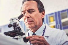 Beschäftigter fleißiger Biologe, der Mikroskop untersucht stockfotografie