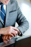 Beschäftigter Geschäftsmann, der seine Armbanduhr bei der Aufwartung betrachtet Stockbild