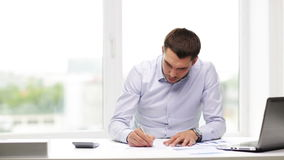 Beschäftigter Geschäftsmann mit Laptop und Papieren im Büro stock video footage