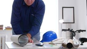 Beschäftigter Ingenieur im Innenbüro offen und einen Bauplan auf dem Schreibtisch analysieren stock video footage