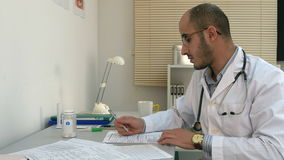Beschäftigter männlicher Arzt, der mit Papieren arbeitet und Telefongespräch in seinem Büro hat stock footage