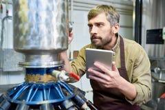 Beschäftigter männlicher Ingenieur, der Brauereiausrüstung in Anlage justiert stockbilder