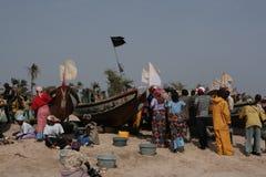 Beschäftigter Strand, wenn Fischerboot zurückgeht - Gambia, Afrika Stockfotografie