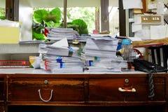 Beschäftigter, unordentlicher und durcheinandergeworfener Arbeitsplatz, voll von den Dokumenten Lizenzfreies Stockbild
