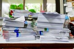 Beschäftigter, unordentlicher und durcheinandergeworfener Arbeitsplatz, voll von den Dokumenten Stockbilder