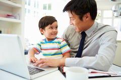 Beschäftigter Vater Working From Home mit Sohn Stockbild