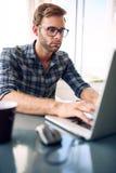 Beschäftigtes Schreiben des Studenten ein Artikel auf seinem Notizbuch Lizenzfreie Stockfotos