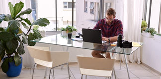 Beschäftigtes von seinem Schreibtisch zu Hause arbeiten des Geschäftsmannes Lizenzfreie Stockfotografie