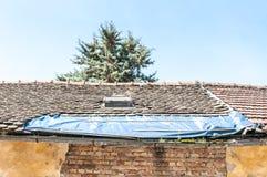 Beschadigd dak met tegels op het oude die huis met plastic nylon wordt behandeld om binnenland tegen regenwater te beschermen royalty-vrije stock afbeeldingen