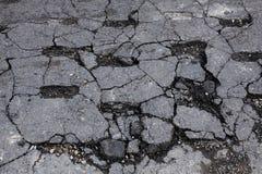 Beschadigd gebarsten asfalt Royalty-vrije Stock Afbeeldingen