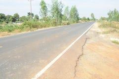Beschadigde asfaltweg in de kant van het land Stock Afbeeldingen