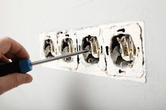 Beschadigde machtsafzet in de muur Elektriciteitsgevaar stock afbeelding
