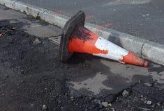 Beschadigde verkeerskegel in goot, weg die reparaties ondergaan stock foto